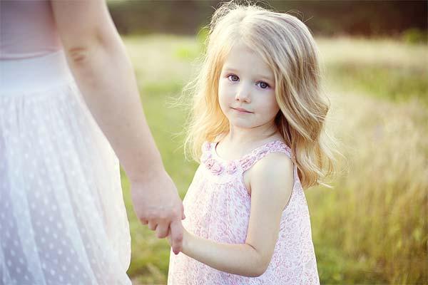 Девочка держит маму за руку