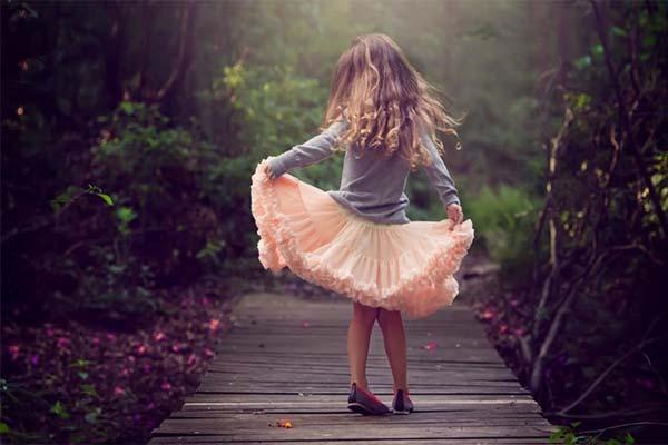 Девочка в розовой юбке на мосту