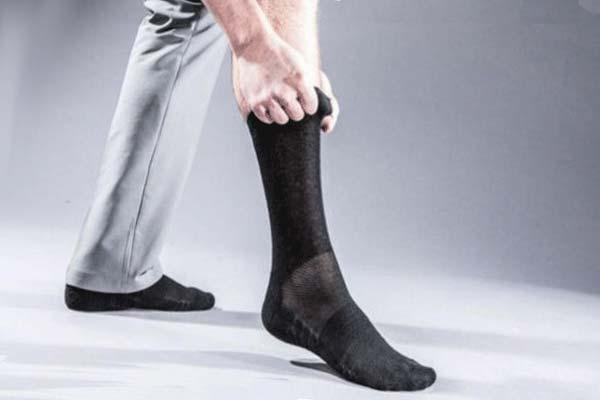 Мужчина надевает носки