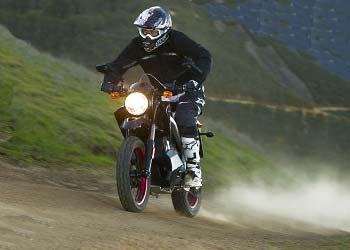Мотоциклист едет по дороге с зажженной фарой