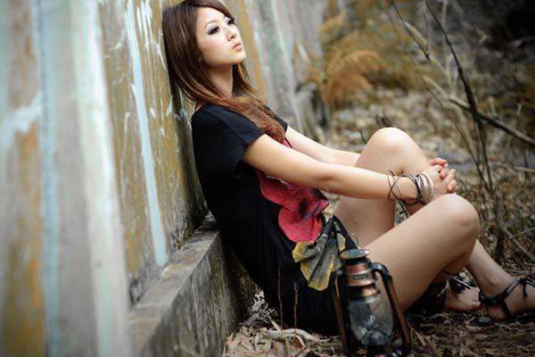 Девушка сидит под забором