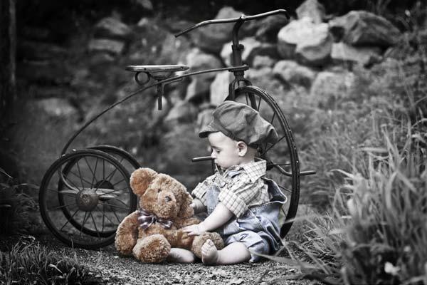 Мальчик с плюшевым мишкой у велосипеда