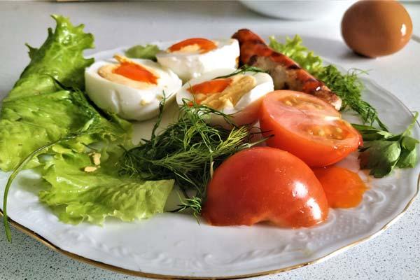 Тарелка с листьями салата и яйцом