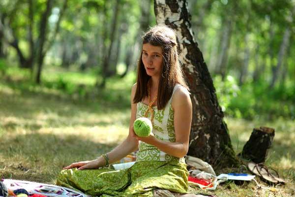 девушка сидит на траве с яблоком
