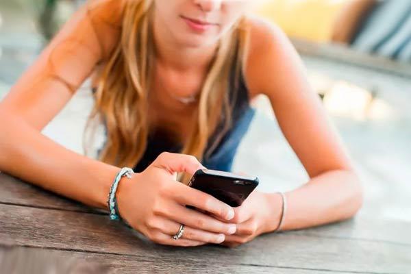 Девушка сидит за столом и смотрит на смартфон