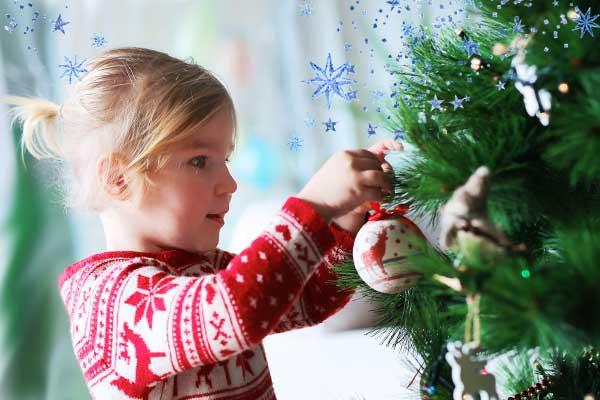 Девочка наряжает елку