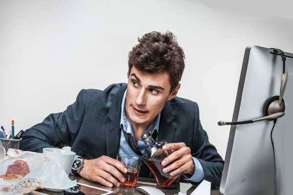 Молодой человек за компьютером в офисе выпивает
