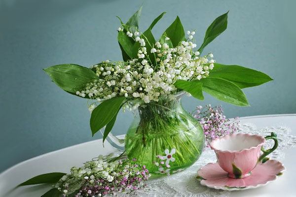 Ландыши в кувшине на столе, застеленном белой скатертью, розовая чашка