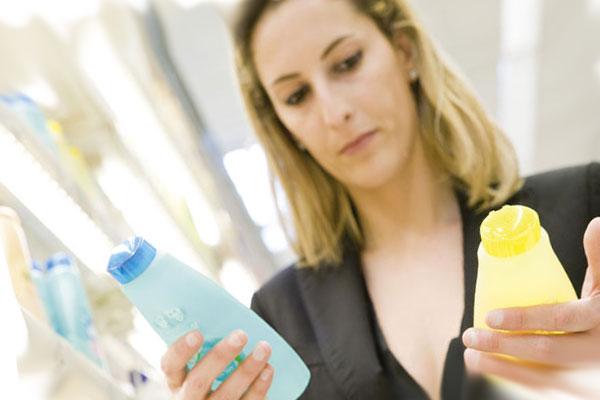 выбор моющего средства, женщина держит в руках два шампуня