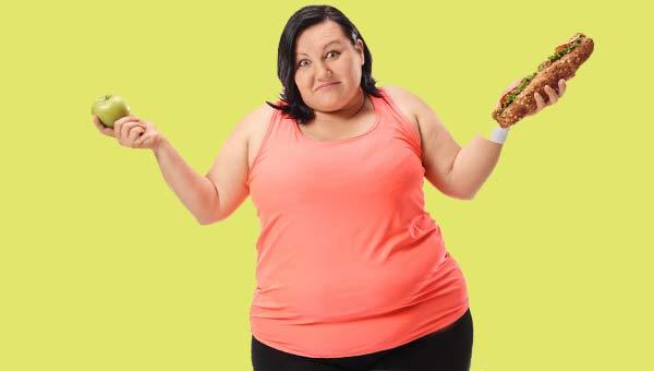 Полная женщина с яблоком и сандвичем