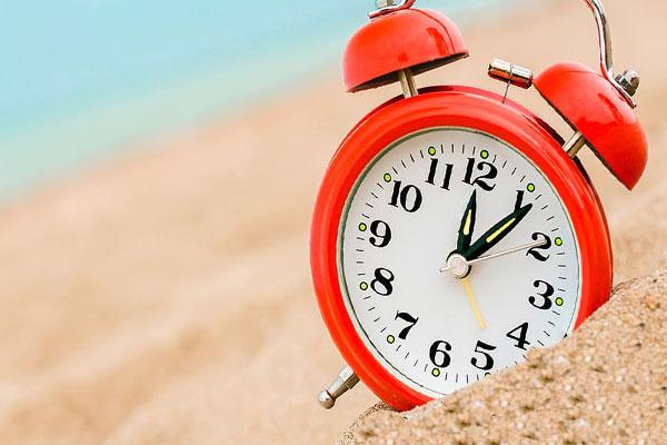 Будильник на песке на пляже