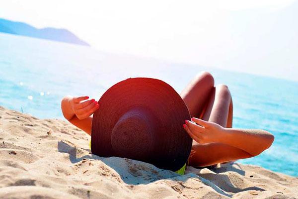 девушка лежит на пляже в шляпе у воды
