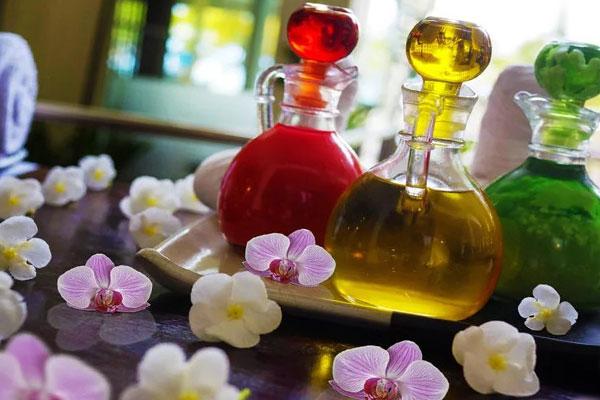 Цветы орхидеи и бутылочки с красным и желтым эфирным маслом