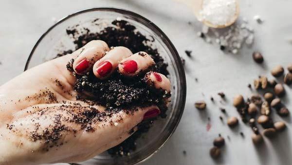 Стеклянная миска с кофейной гущей, рука с маникюром, кофейные зерна
