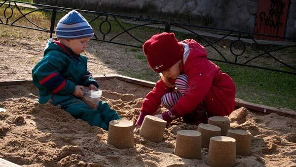 Мальчик и девочка играют в песочнице