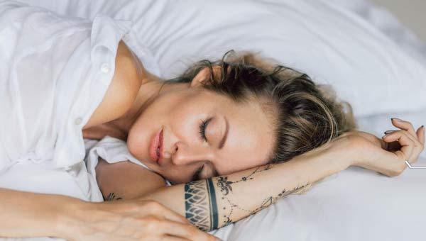 Девушка с татуировкой на руке в кровати спит